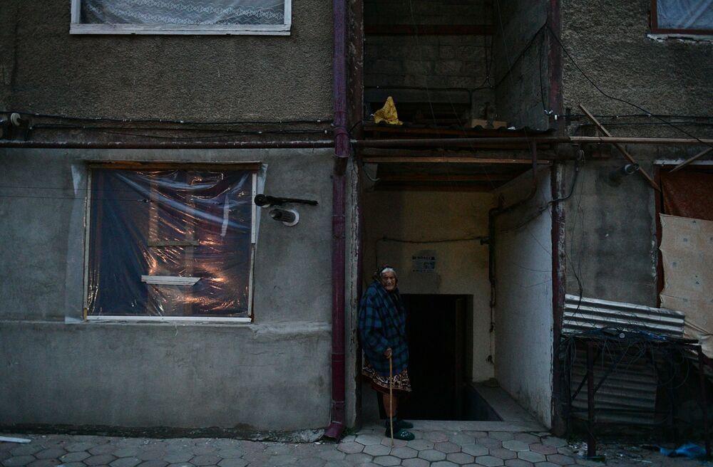 Una donna anziana vicino a una casa a Stepanakert