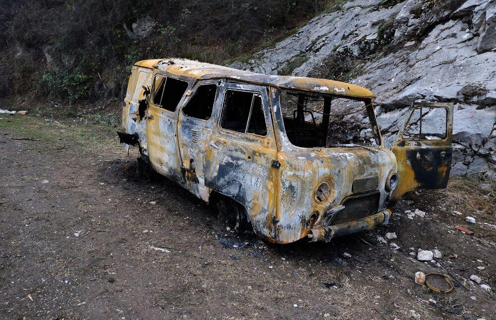 Un'auto danneggiata da un bombardamento sul ciglio di una strada nel Nagorno-Karabakh
