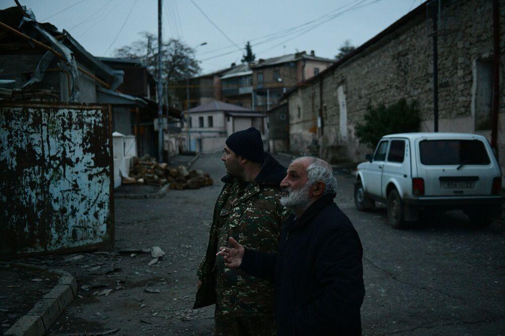 Uomini vicino a una casa distrutta a Stepanakert