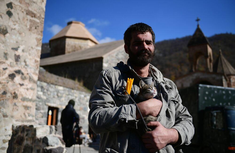 Un uomo con un gatto vicino alla chiesa del monastero di Dadivank nel Nagorno-Karabakh