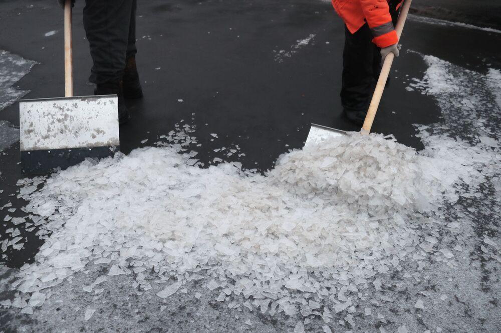 I dipendenti dei servizi pubblici puliscono una strada dopo una pioggia gelata caduta a Mosca.