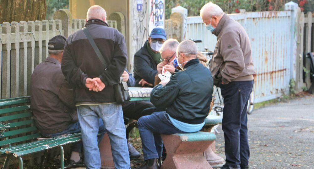 I pensionati giocano a carte in una strada
