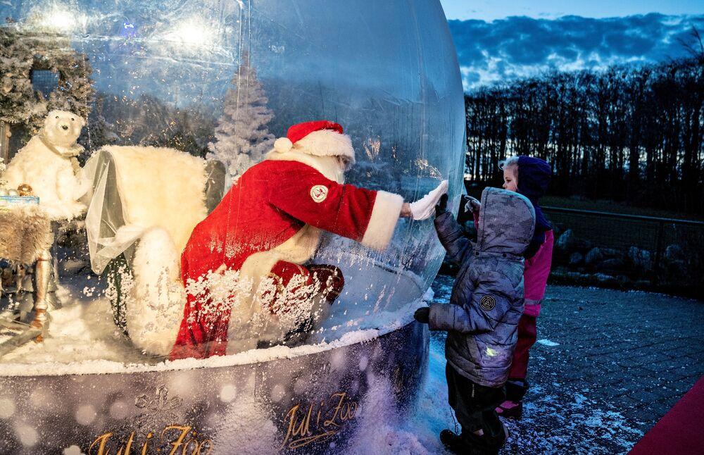 Babbo Natale incontra i bambini trovandosi in una particolare bolla di Babbo Natale per evitare eventuali contagi durante il periodo di Coronavirus, Aalborg, Danimarca, il 13 Novembre 2020.