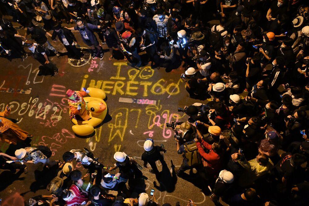 I rappresentanti dei media fotografano un clown su una gigantesca anatra gonfiabile durante una manifestazione antigovernativa a Bangkok, Thailandia, il 18 Novembre 2020.