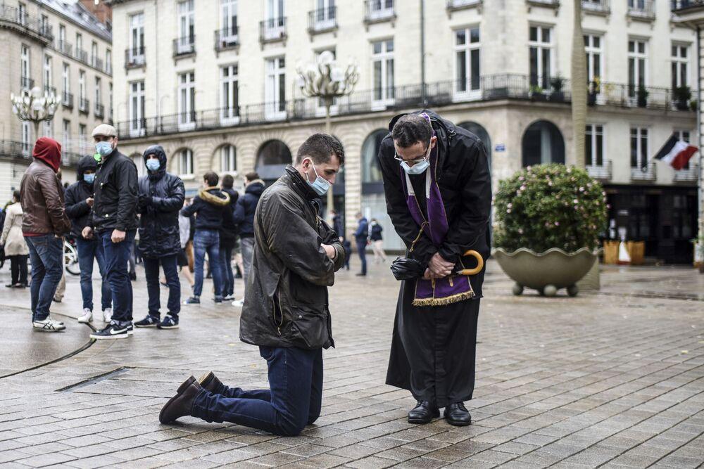 Un prete cattolico ascolta la confessione di un uomo durante un raduno per chiedere la riapertura dei luoghi di culto chiusi a causa del coronavirus, Nantes, Francia, il 15 Novembre 2020.