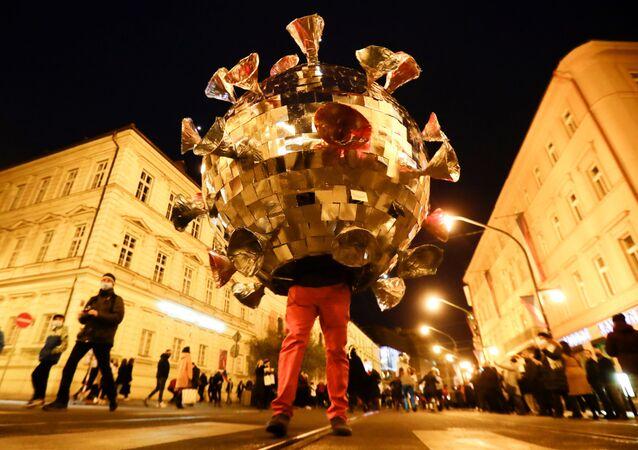 Un uomo vestito da Coronavirus protesta contro le restrizioni anti-Covid a Praga, il 17 Novembre 2020.