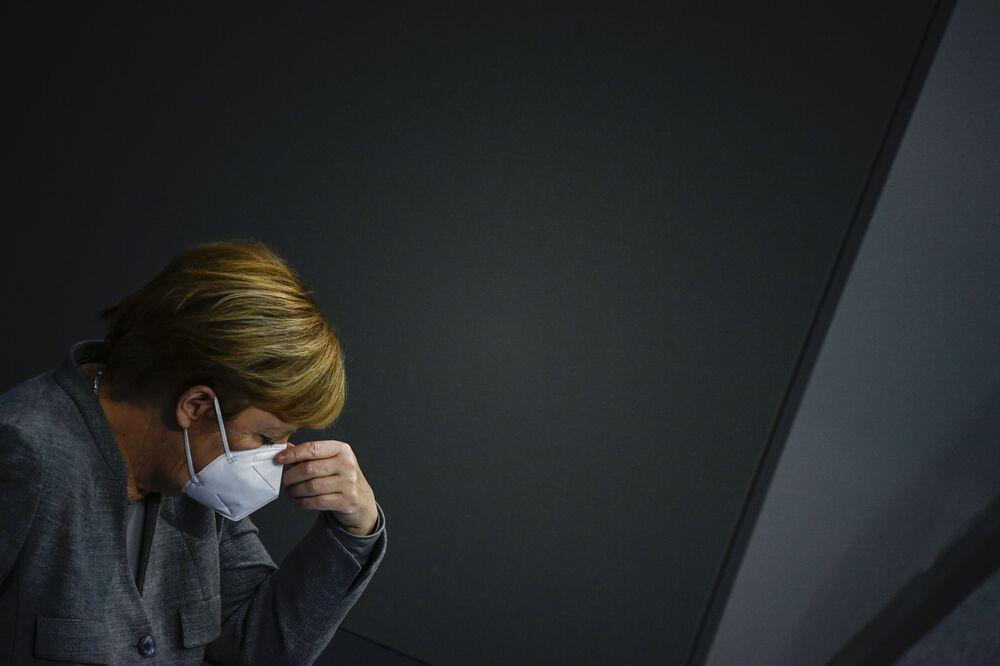 La cancelliera tedesca Angela Merkel riordina la mascherina durante una riunione del Bundestag, Germania, il 18 Novembre 2020.