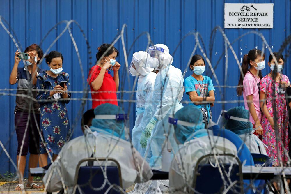 Gli operai si sono messi in fila aspettando la possibilità di  fare il tampone di coronavirus, Malaysia, il 18 Novembre 2020.