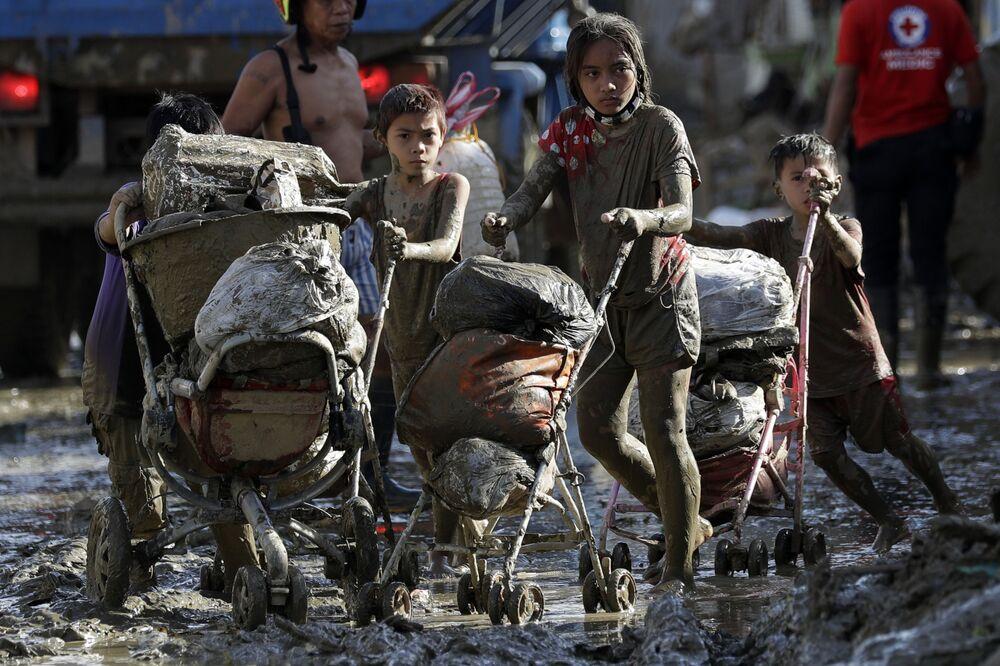 I bambini spingono i carrelli pieni di oggetti dalle loro case colpite dal tifone Vamco, Filippine, il 17 Novembre 2020.