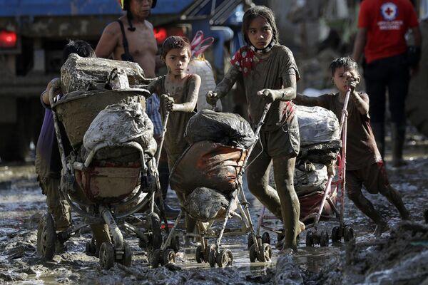 I bambini spingono i carrelli pieni di oggetti dalle loro case colpite dal tifone Vamco, Filippine, il 17 Novembre 2020.  - Sputnik Italia