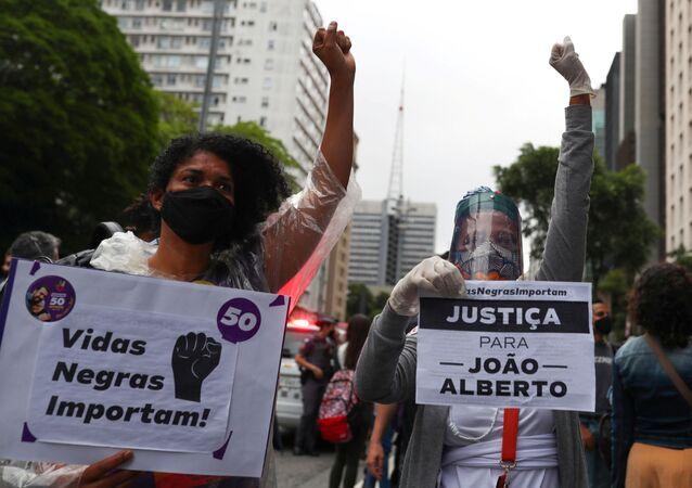 Manifestanti reggono cartelli con la scritta Black Lives Matter (L) e Giustizia per Joao Alberto durante una marcia a San Paolo in occasione della Giornata nazionale della coscienza nera e in segno di protesta contro la morte di Joao Alberto Silveira Freitas, un uomo nero picchiato a morte in un supermercato a Porto Alegre, Brasile, 20 novembre 2020