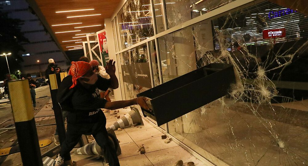 A demonstrator damages a storefront during a march in Sao Paulo on National Black Consciousness Day and in protest against the death of Joao Alberto Silveira Freitas, a Black man beaten to death at a market in Porto Alegre, Brazil, November 20, 2020