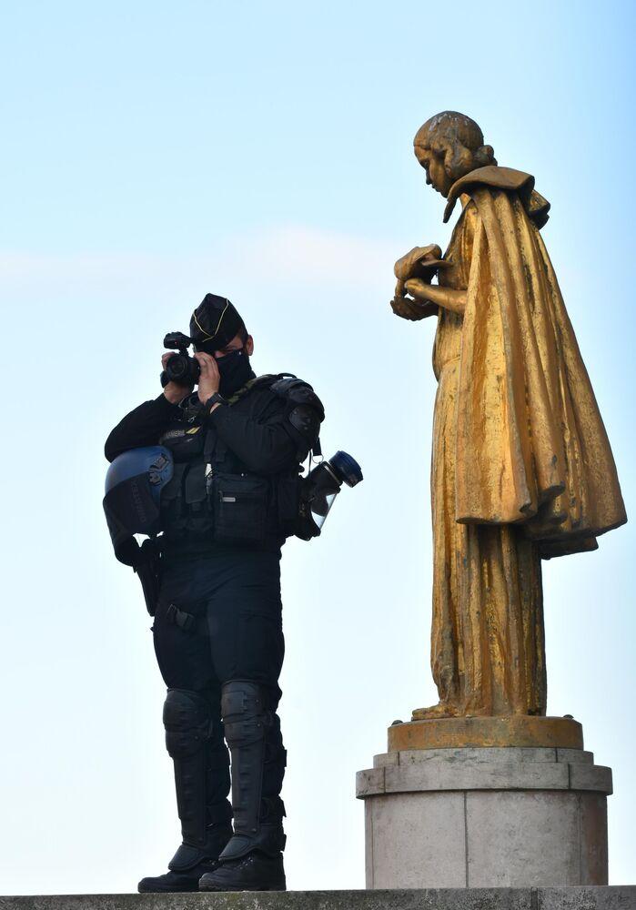 Un agente di polizia filma le proteste contro l'articolo 24 del disegno di legge sulla sicurezza globale a Parigi.