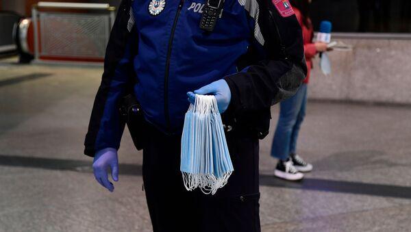 Un poliziotto distribuisce maschere alla stazione di Atocha a Madrid - Sputnik Italia