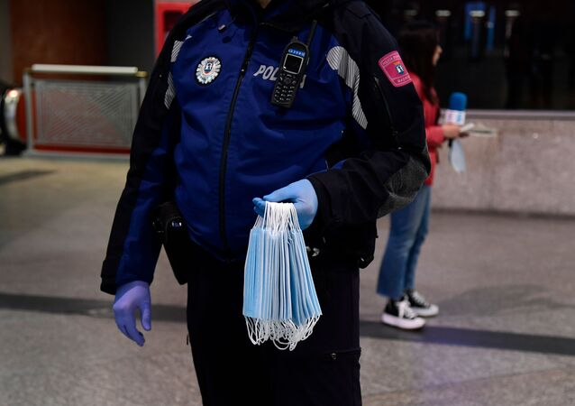 Un poliziotto distribuisce maschere alla stazione di Atocha a Madrid