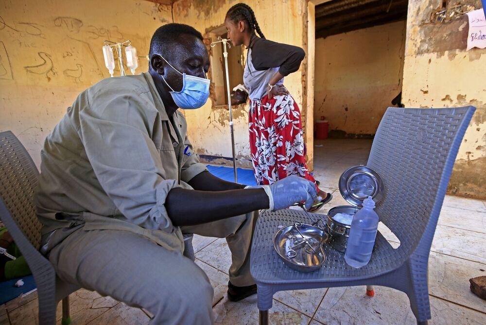Un medico disinfetta gli strumenti chirurgici in un campo profughi
