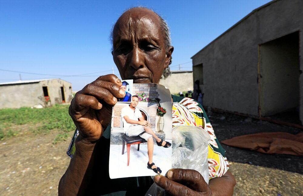 Una donna etiope mostra le foto dei suoi parenti