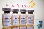 Vials with a sticker reading, COVID-19 / Coronavirus vaccine / Injection only and a medical syringe are seen in front of a displayed AstraZeneca logo in this illustration taken October 31, 2020.