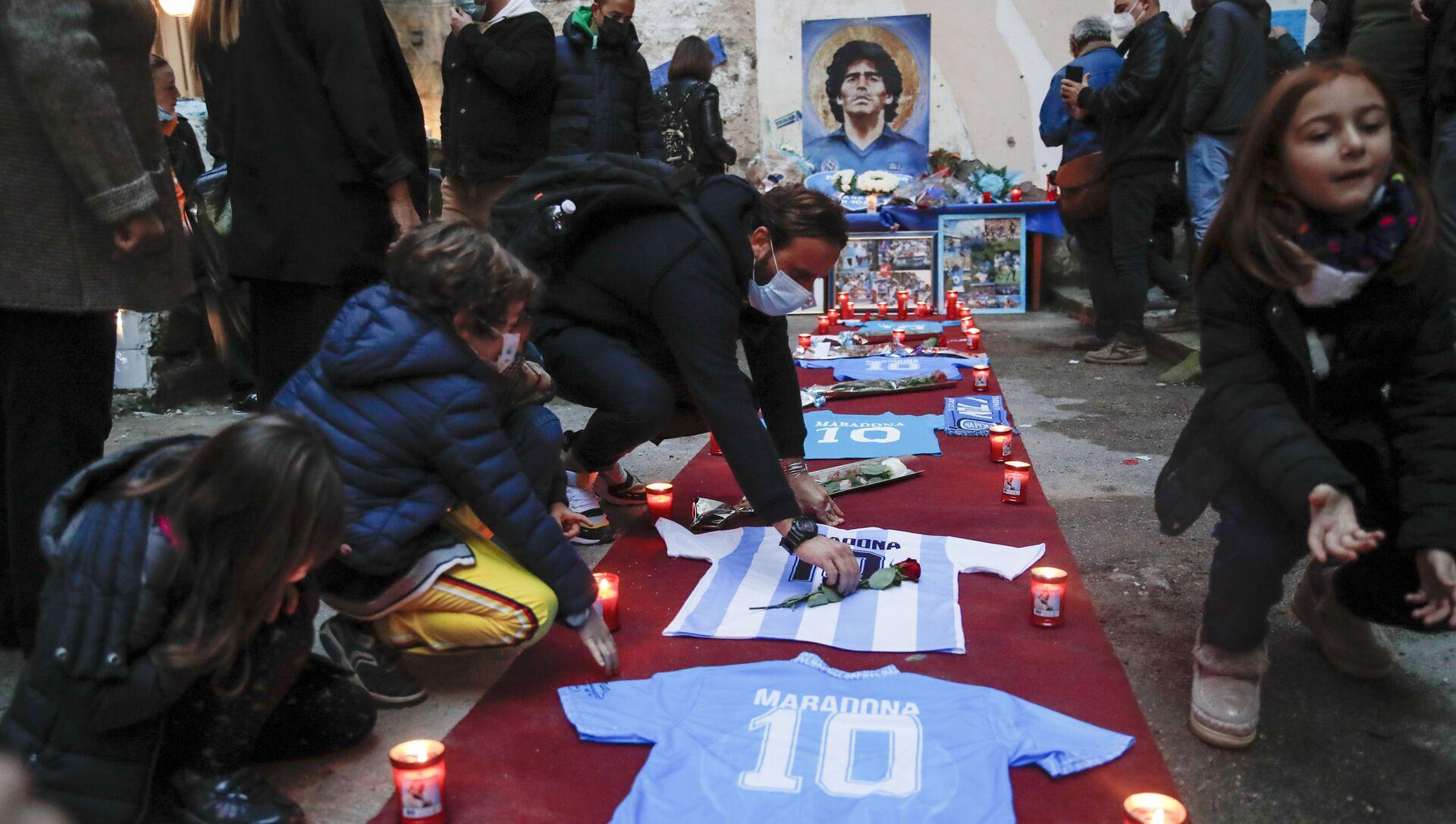 Le persone accendono le candele per onorare la memoria di Diego Maradona in Quartieri Spagnoli di Napoli - Sputnik Italia, 1920, 20.04.2021