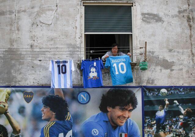 Una donna appende una maglietta con il numero 10 e la scritta Diego Maradonna su una corda in Quartieri Spagnoli di Napoli