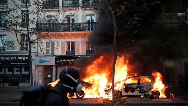 Cars burn during a demonstration against the Global Security Bill that rights groups say would make it a crime to circulate an image of a police officer's face and would infringe journalists' freedom in France, in Paris, November 28, 2020. - Sputnik Italia
