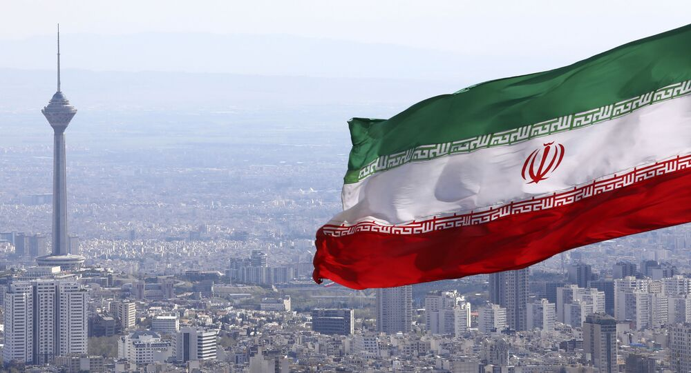 In this March 31, 2020, file photo, Iran's national flag waves as Milad telecommunications tower and buildings are seen in Tehran, Iran