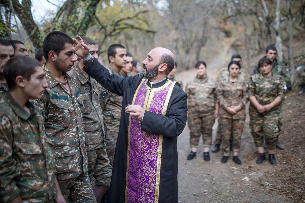 Il sacerdote Aristakes Hovhannisyan durante una cerimonia di battesimo per i militari vicino alla linea del fronte in Nagorno-Karabakh.