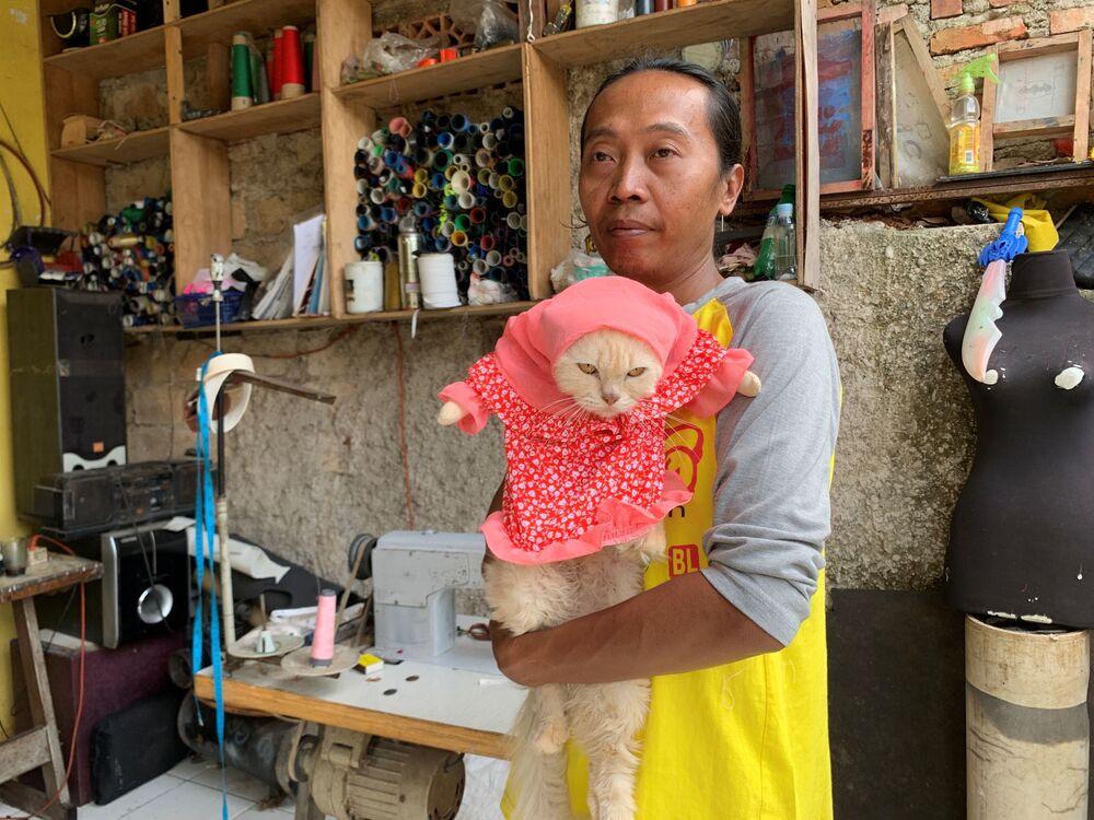 Fredi Lugina Priadi, 39 anni, stilista indonesiano, con il suo gatto che indossa un costume cosplay, Giacarta, Indonesia, il 26 novembre 2020