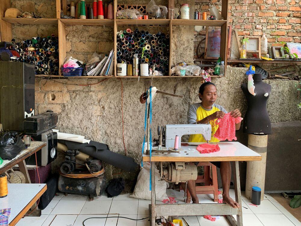 Fredi Lugina Priadi, 39 anni, un creatore di costumi cosplay per gatti, cuce un costume a Giacarta, Indonesia, il 26 novembre 2020
