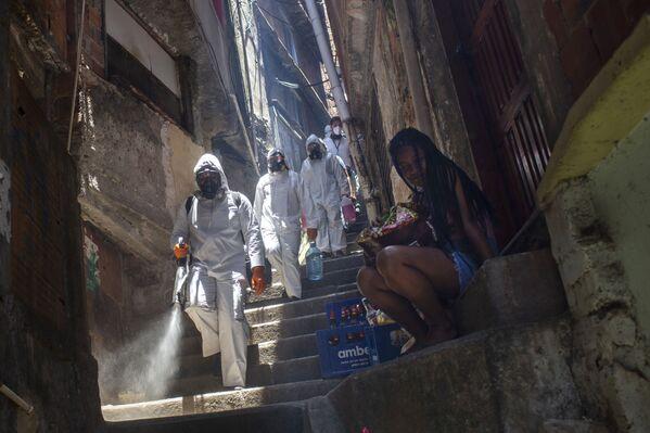 Volontari disinfettano i vicoli degli slum di Santa Marta a Rio de Janeiro, Brasile - Sputnik Italia