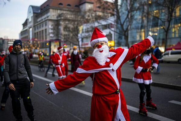 Persone in costumi da Babbo Natale su pattini a rotelle e biciclette durante una processione a Berlino - Sputnik Italia