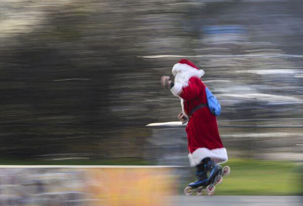 Uomo in costume da Babbo Natale sui pattini a rotelle in Germania - Sputnik Italia