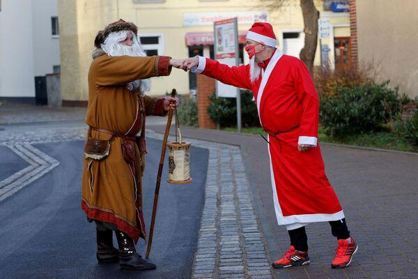 Un uomo vestito da Babbo Natale indossa una maschera protettiva prima di correre per le strade di Michendorf, vicino a Berlino, durante Nikolaus Lauf (corsa di San Nicola), Germania, il 6 dicembre 2020 - Sputnik Italia
