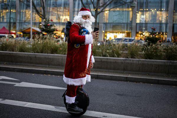 Uomo vestito da Babbo Natale su una monoruota a Berlino - Sputnik Italia