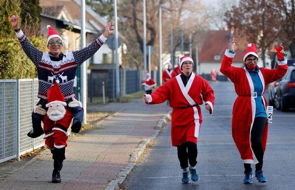 Persone vestite da Babbo Natale corrono per le strade di Michendorf, vicino a Berlino, durante Nikolaus Lauf (corsa di San Nicola), Germania, il 6 dicembre 2020 - Sputnik Italia