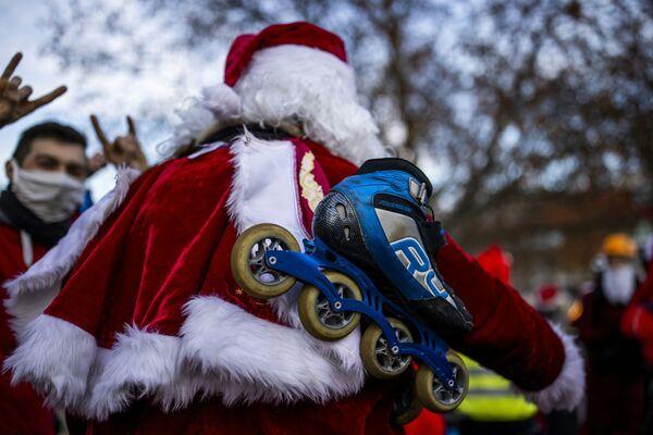 Pattinatori a rotelle e ciclisti vestiti con abiti da Babbo Natale si fanno strada lungo il viale Kurfuerstendam a Berlino il 6 dicembre 2020 - Sputnik Italia