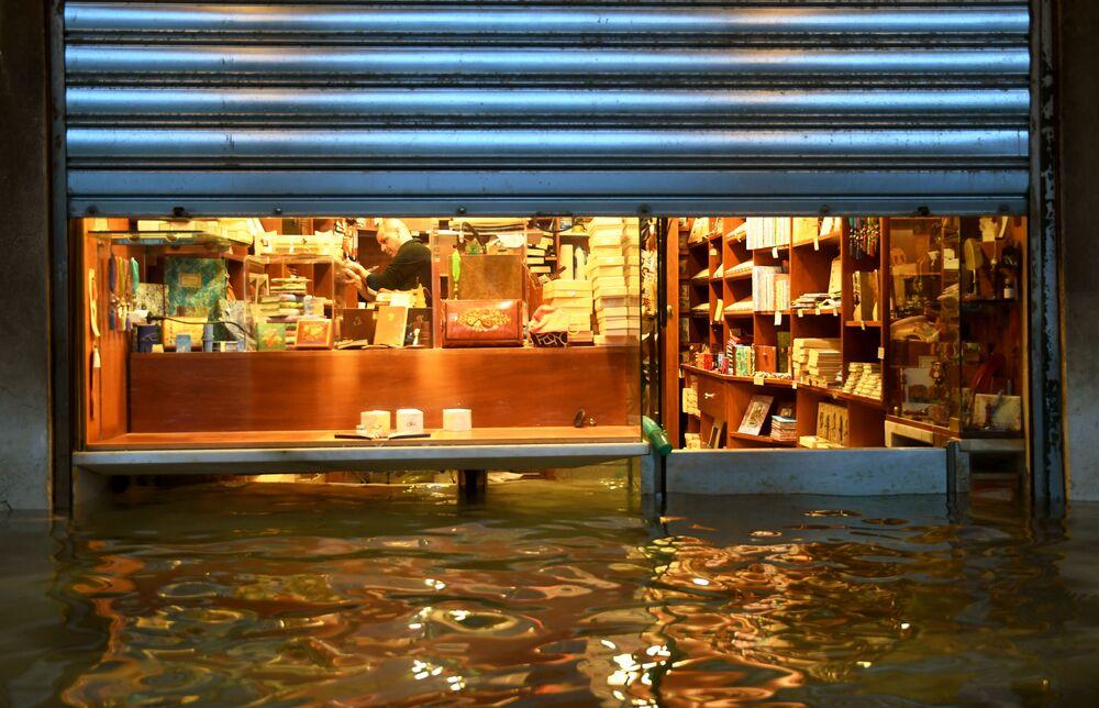 Il proprietario di un negozio vicino a Piazza San Marco a Venezia cerca di proteggere il locale dalle inondazioni
