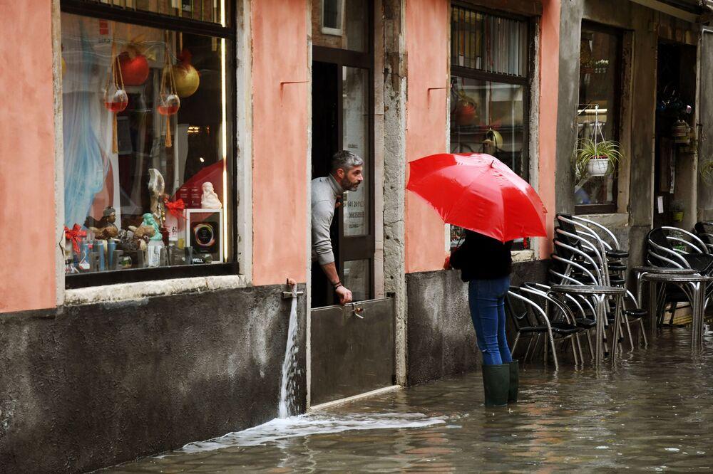 Un negoziante cerca di proteggere il suo locale dall'acqua a Venezia, l'8 dicembre 2020