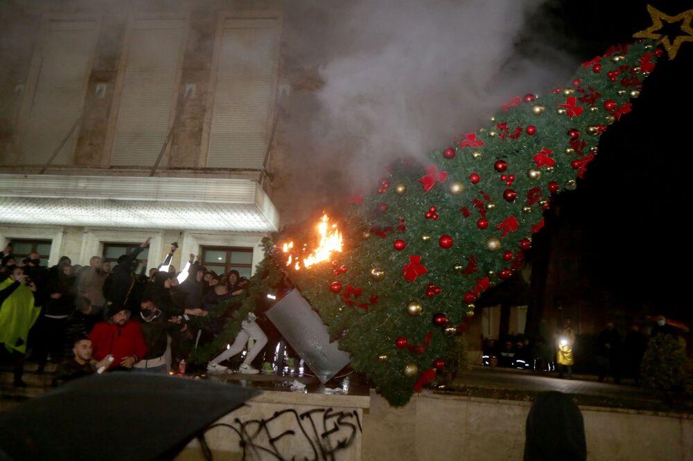 I manifestanti bruciano un albero di Natale davanti all'ufficio del primo ministro albanese durante gli scontri a Tirana
