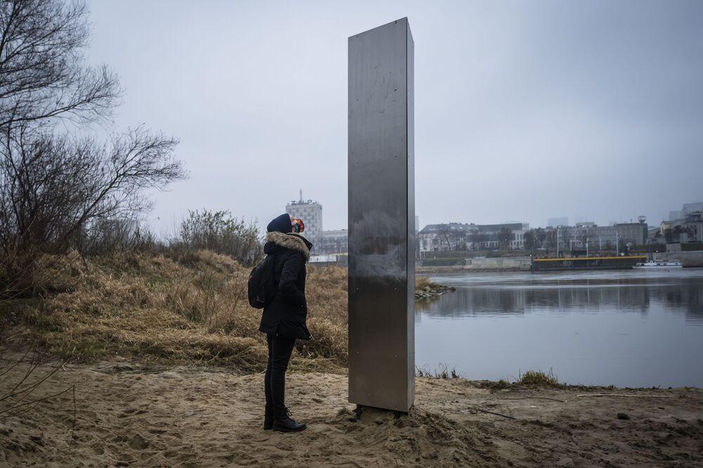 Una donna ammira un monolite di metallo misterioso apparso nella capitale polacca Varsavia