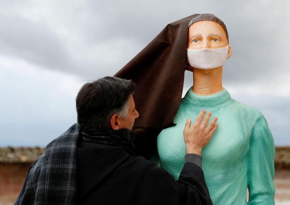 Un prete con una figura di infermiera davanti alla chiesa di San Francesco ad Assisi, Italia
