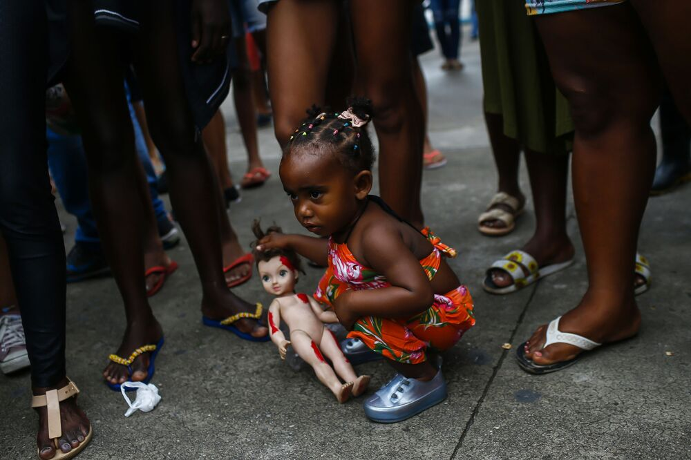 Una ragazza con una bambola durante una protesta a Duque de Caxias, Brasile