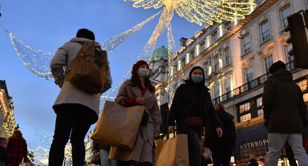 Christmas lights twinkle above shoppers and pedestrians walking along Regent Street in London on December 12, 2020, as with under two weeks to Christmas, people take advantage of the easing of England's restrictions on shop openings to combat the spread of the novel coronavirus.