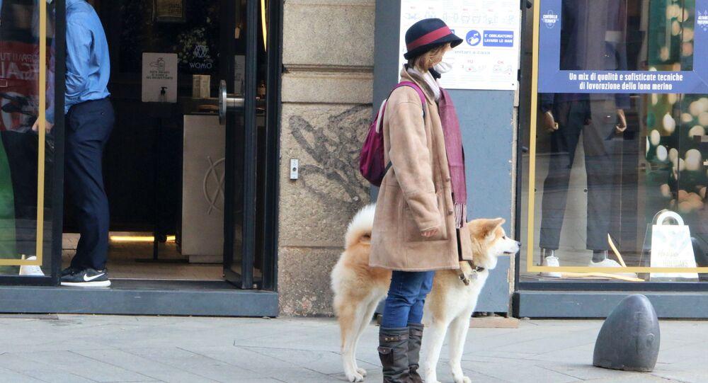 Una donna in mascherina con un cane