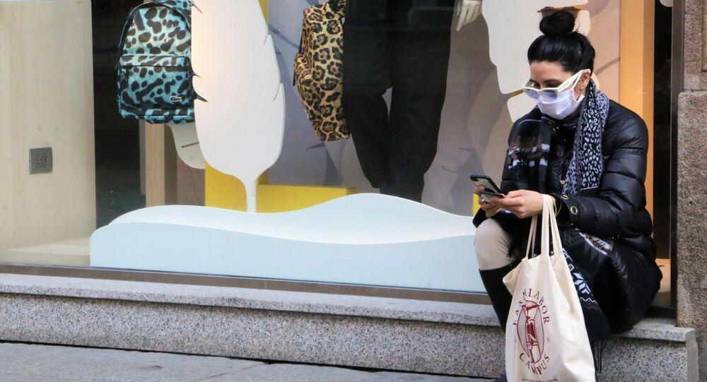 Una donna in mascherina vicino a un negozio