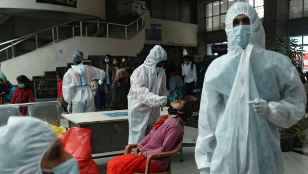 A health worker in personal protective equipment (PPE) collects a swab sample from a woman during a rapid antigen testing campaign for the coronavirus disease (COVID-19), at a railway station in Mumbai, India, December 11, 2020 - Sputnik Italia