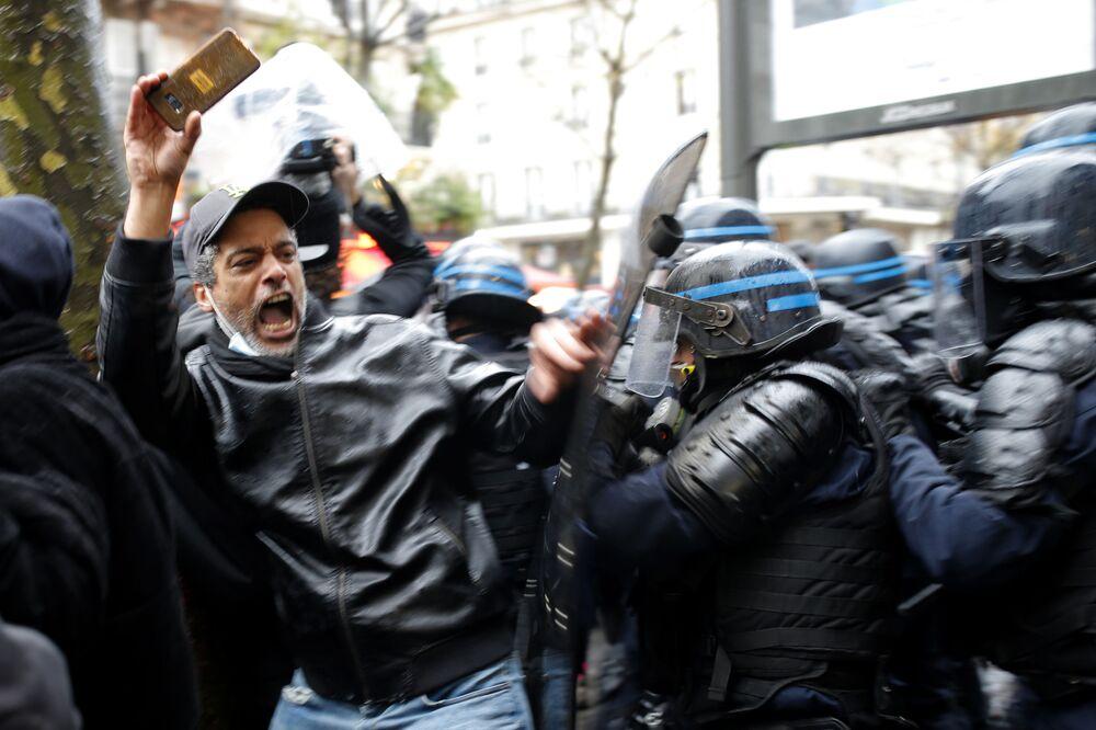 Un manifestante e i poliziotti a Parigi nel corso delle proteste contro la legge sulla sicurezza, il 12 Dicembre 2020.