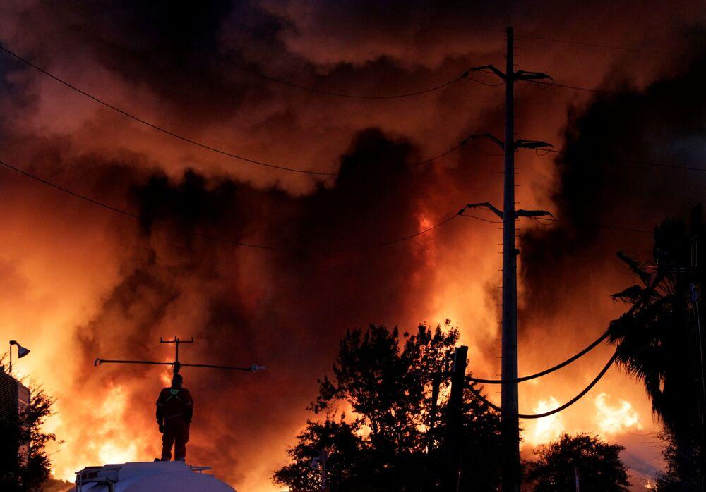 Un vigile del fuoco su un'autopompa durante un incendio nell'impianto di riciclaggio per rottami metallici di Deacero a Guadalupe, alla periferia di Monterrey, in Messico, il 16 Dicembre 2020.