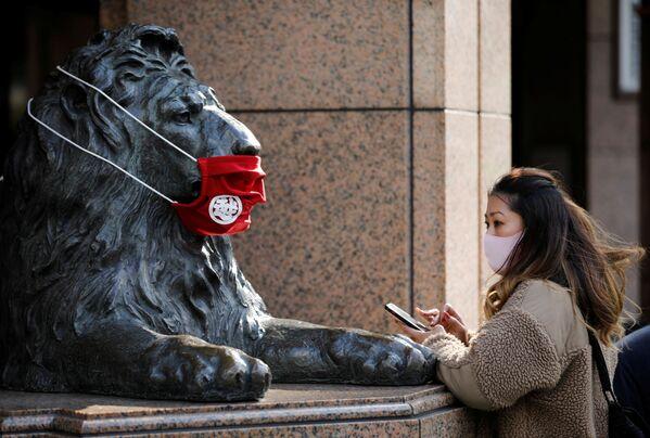 Una donna in mascherina sta davanti ad una statua a Tokyo, Giappone, il 14 Dicembre 2020.  - Sputnik Italia