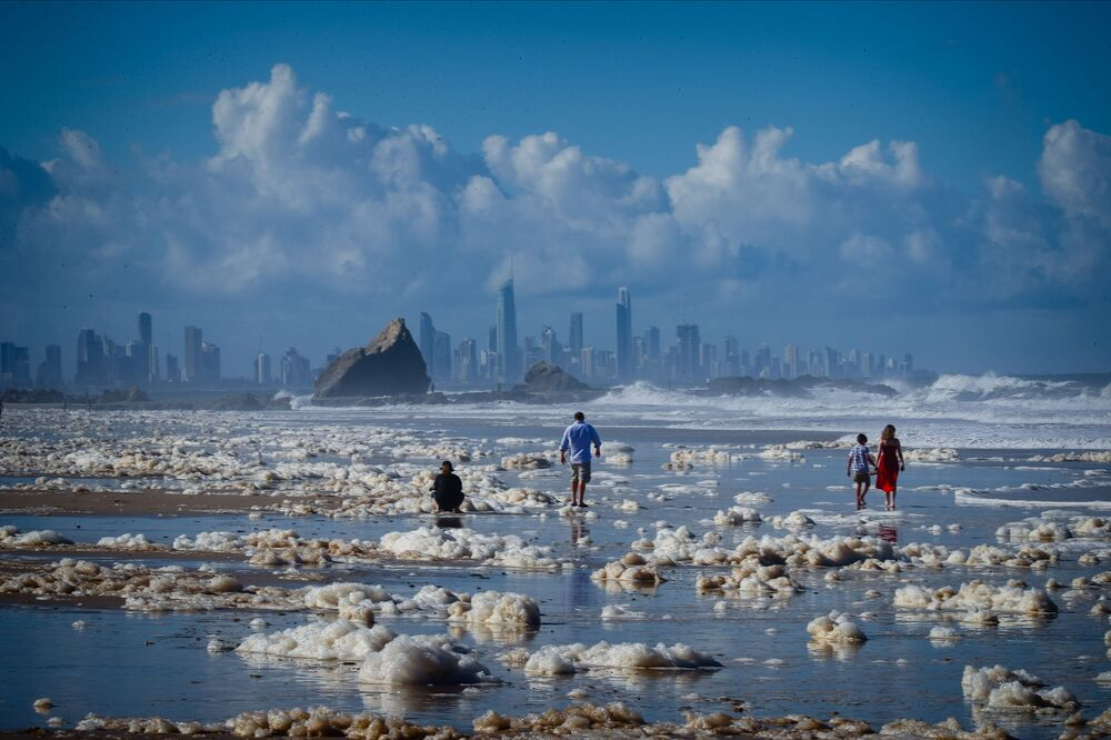 I turisti fanno una passeggiata in mezzo alla schiuma su una spiaggia dell'Australia dopo una tempesta, il 15 Dicembre 2020.
